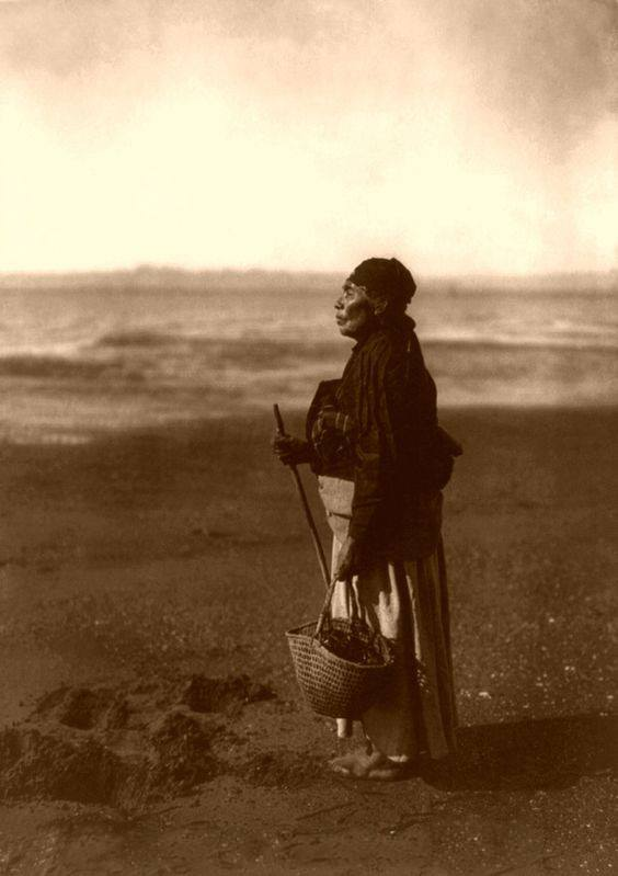 Chinook Woman digging clams at low tide close to Seaside. Edward Curtis 1910